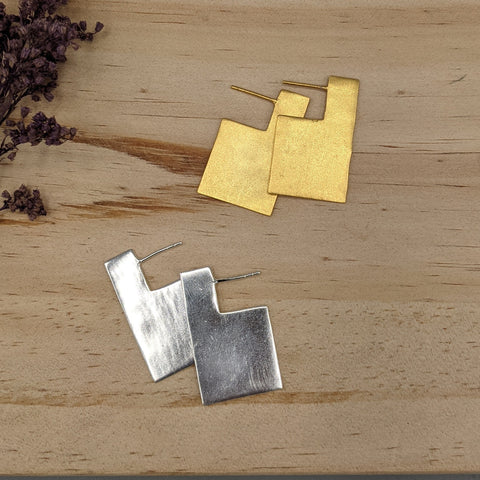 "Shiny gold or silver one-dimensional rectangle with a modern side-facing profile, about 1.5"" long"