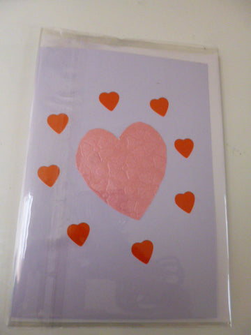 Pink heart card with eight red hearts around it.