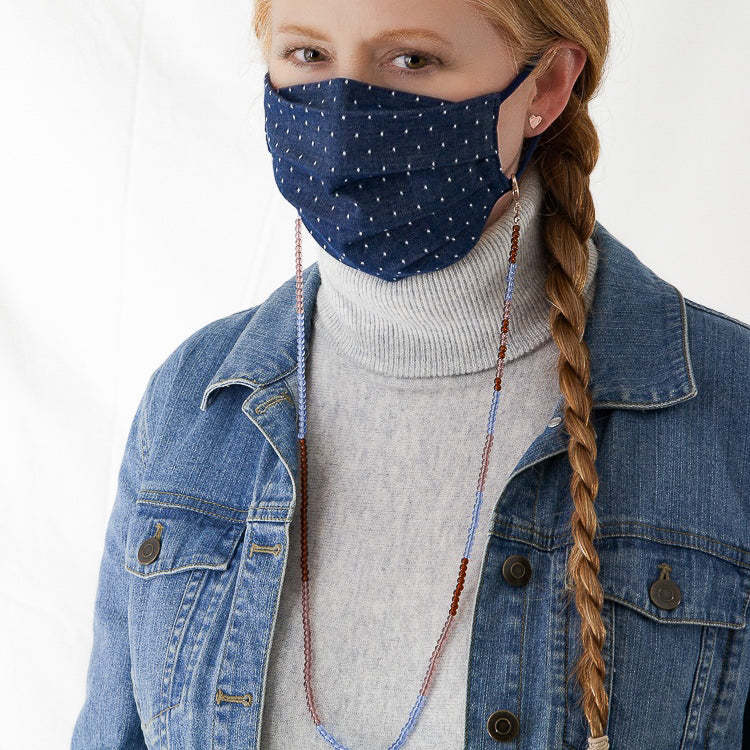 Kelli Ronci wears the CORDA Denim Dot mask and translucent color block glass beaded mask chain. In Rust, Mauve and Cerulean. Flipping the mask chain forward so it's  a necklace, this accessory also doubles as a wrap bracelet when it's not keeping track of your mask. Pandemic Fashion.