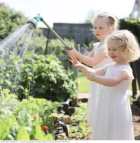 girls watering plants in the garden