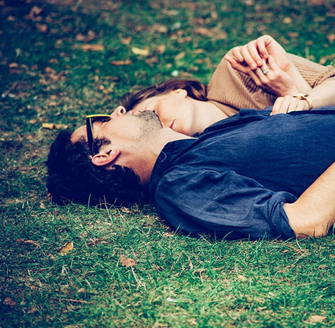 man and woman sleeping on the grass
