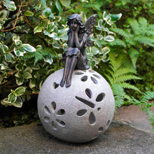 Sitting fairy garden solar light ornament in garden.