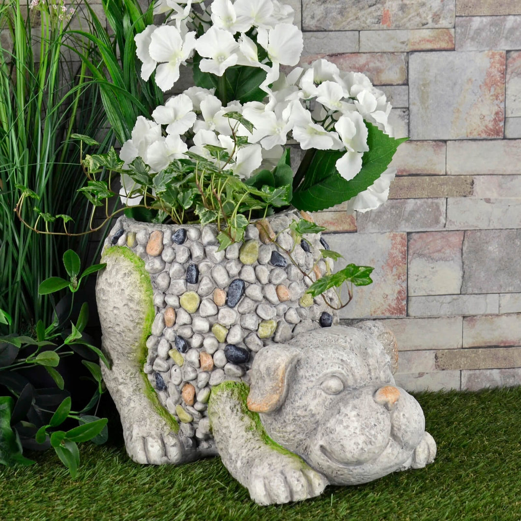 crouching dog garden planter in grey and brown mosaic pebble design filled with white flowers and ivy in a garden