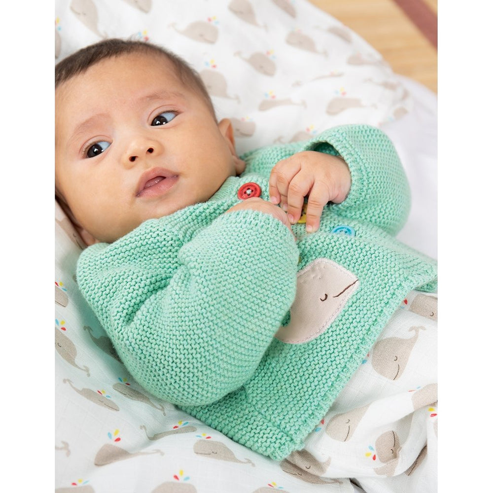 Baby wearing Frugi Cute as a Button Aqua Whale Cardigan with Eloween Dungarees