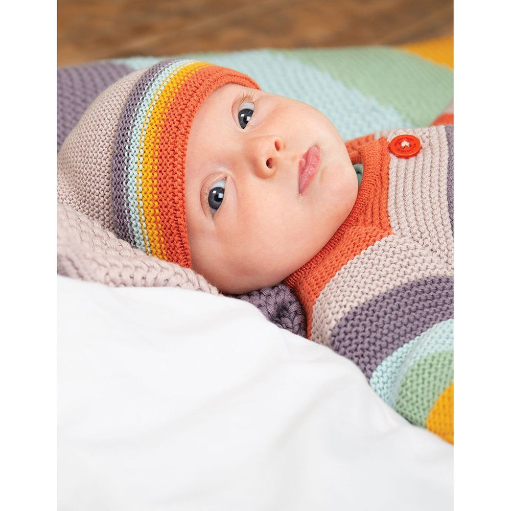 Baby wearing Frugi cute as a button knitted baby cardigan - soft rainbow
