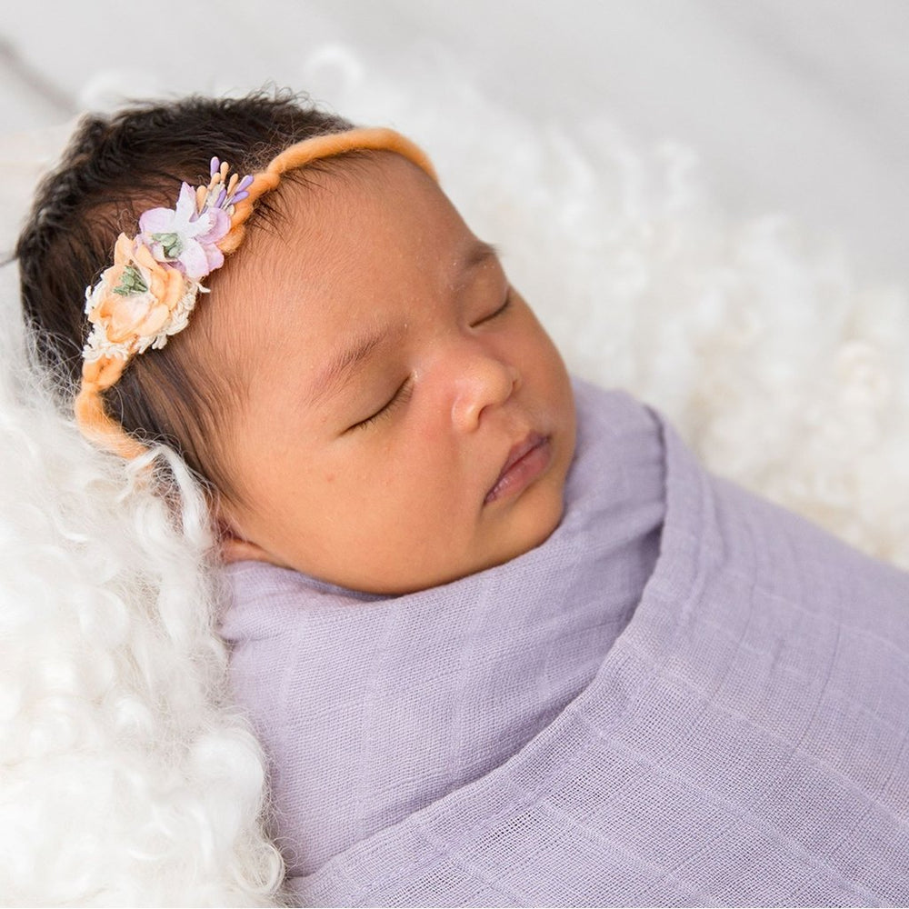 Close up of baby in Love & Lee organic muslin wrap lilac