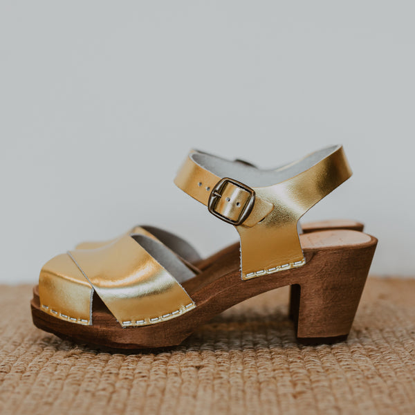 Gold metallic cross over sandal clog with ankle strap and a mid heel