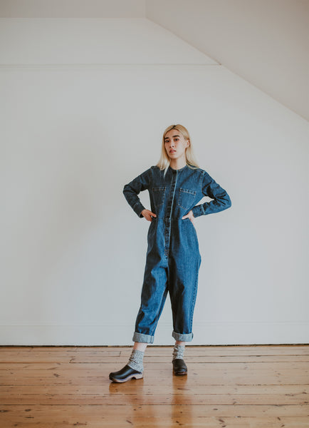woman wears denim jumpsuit with thick socks and black low classic style swedish clog