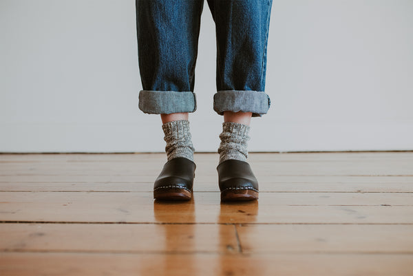 close up of woman's feet in denim jumpsuit with thick socks and black low classic style swedish clog