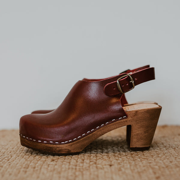 garnet oxblood maroon coloured covered swedish clog with a strap to the back and a mid heel