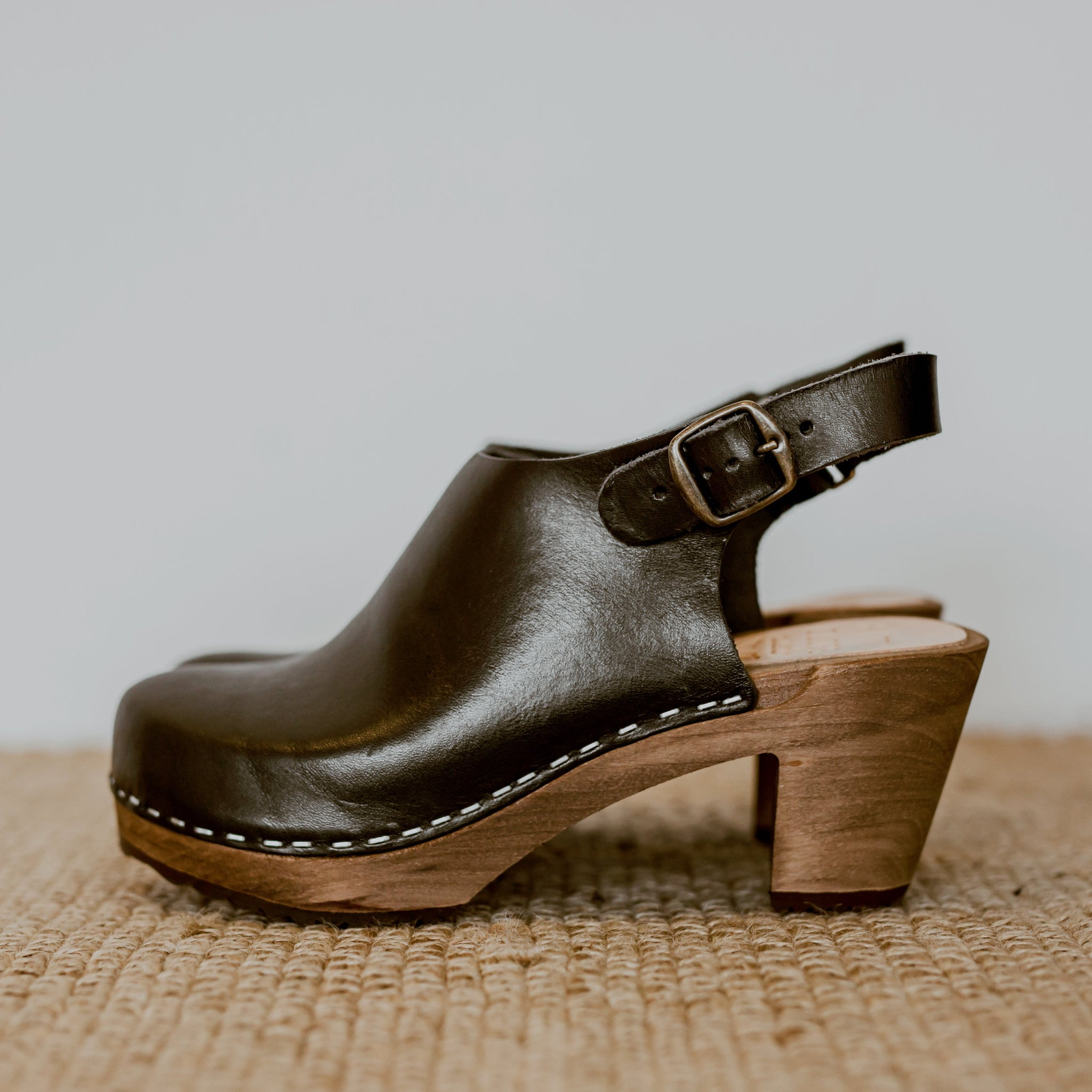 onyx black classic style swedish clog with a mid heel and a strap to the back