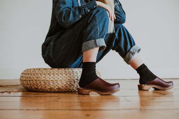 girl wears denim jumpsuit with her socks in onyx and garnet low Klassisk clog
