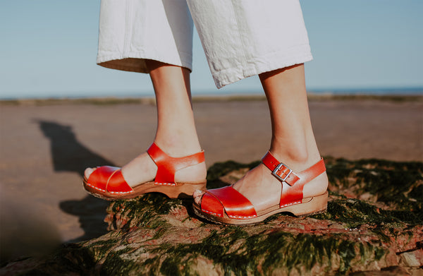 woman wears brandy red leather low cross over dansare clog sandal