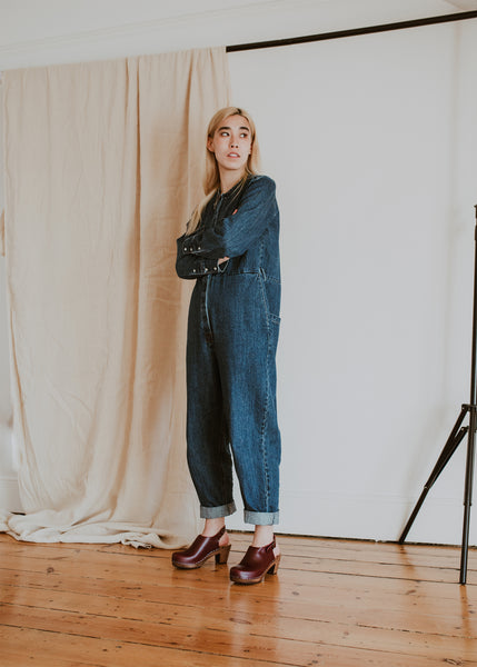girl wears denim jumpsuit with garnet mid heel classic clogs with a strap to the back