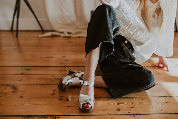girl poses wearing a white shirt and black wide leg jeans with silver cross over mid heel clog sandals