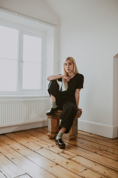 girl wears black jeans with sage green ribbed ankle socks and onyx low heel clog shoe