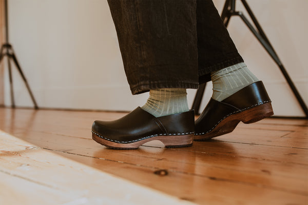 close up of woman's feet in sage green ribbed ankle socks and onyx low heel clog shoe