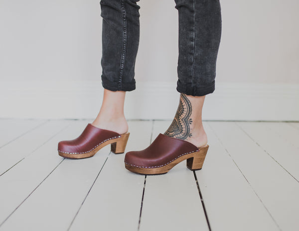 close up of woman's feet wearing mid heel garnet klassisk women's swedish clogs