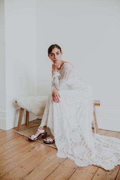 bride wears full length lace dress with bridal wedding silver leather woven cross over clog sandals
