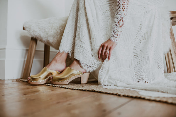 bride wearing a full length lace wedding dress with gold classic-style peep toe wedding clogs
