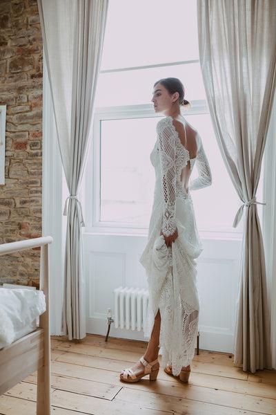bride wears full length lace dress with bridal wedding natural leather woven cross over clog sandals