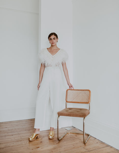bride wearing a feathered top and white, wide leg bridal trousers with bridal wedding gold classic-style swedish clogs
