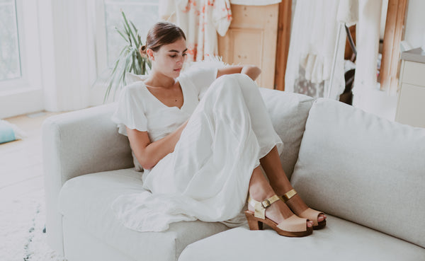 young bride sits on a sofa in her wedding dress and two tone natural and gold bridal clogs
