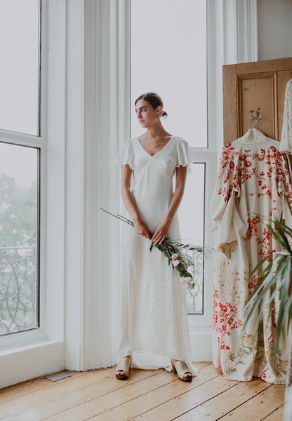 bride stands infront of window in 30's-style wedding dress and bridal wedding classic style stone swedish clog with a peep toe