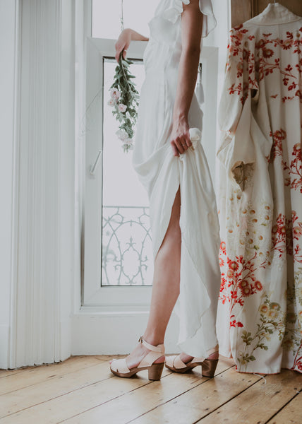 bride standing by window wearing bridal wedding natural leather clog sandals with a mid heel and an ankle strap