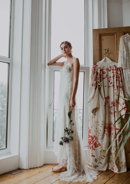 young bride stands by a window wearing stone coloured peep toe bridal clogs with a white lace wedding dress and thistle