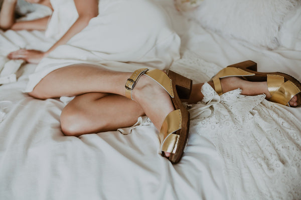 close up of bride wearing bridal wedding gold leather clog sandals with a mid heel and an ankle strap