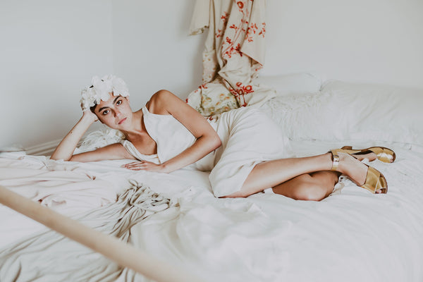 bride lies on bed wearing flower headpiece and bridal wedding gold leather clog sandals with a mid heel and an ankle strap