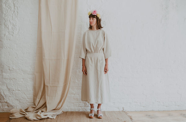 bride wears linen dress flower crown and silver woven clog sandals