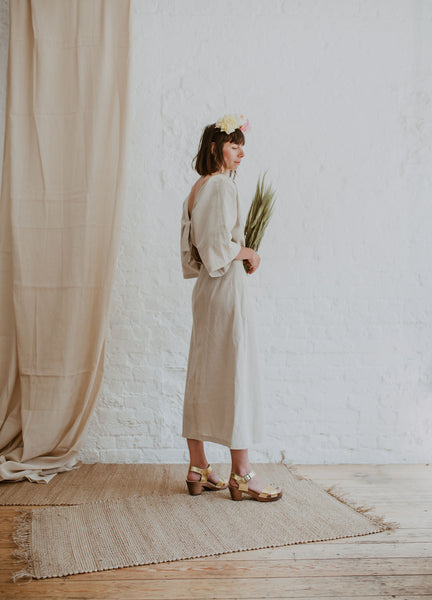 bride wears linen dress with flower crown and grasses bouquet with bridal wedding gold leather crossover sandal swedish clog