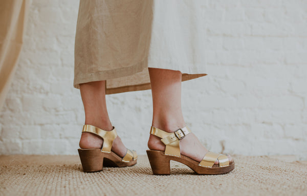 close up of woman's feet in Gold metallic cross over sandal clog with ankle strap and a mid heel