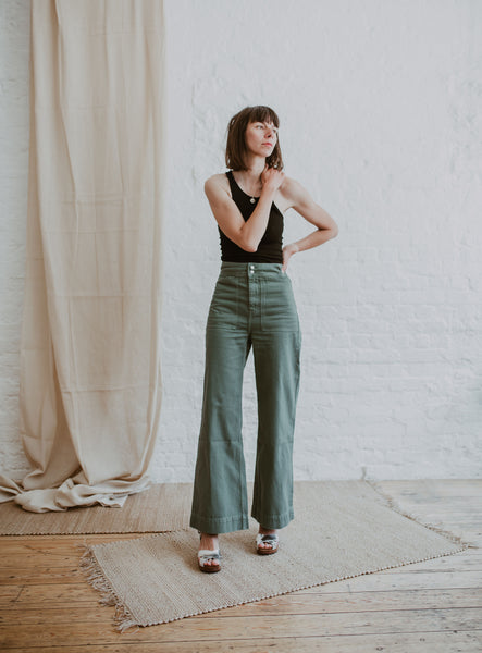 Woman wears high waisted sage green wide legged jeans with silver metallic cross over mid heel sandal clog with ankle strap