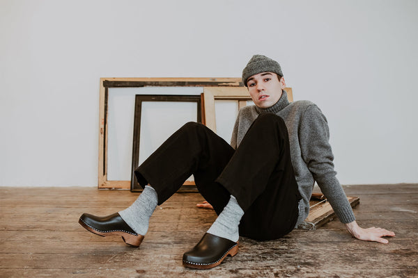 Man poses in a beanie and jumper with black trousers woolly socks and black low heel classic style swedish clogs