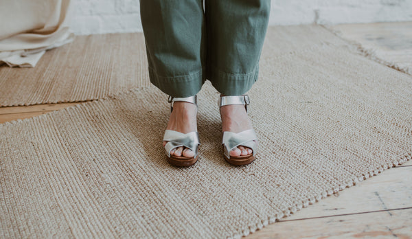 close up of woman's feet in green wide legged jeans with silver metallic cross over mid heel sandal clog with ankle strap