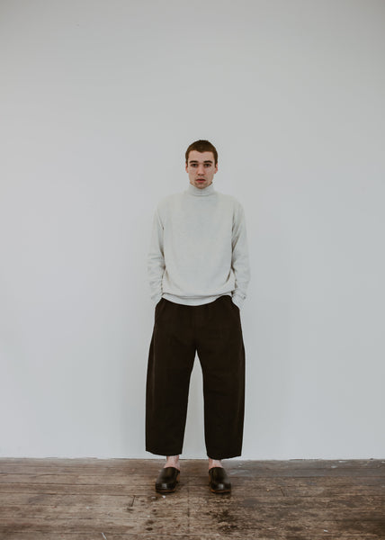 Man poses in a jumper with black trousers and black low heel classic style swedish clogs