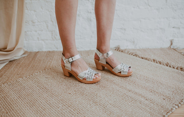 close up of bride's feet wearing bridal wedding silver woven swedish clog sandals