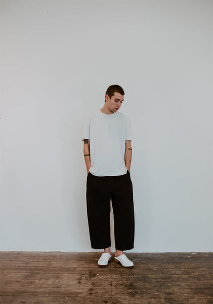 man wears a white tshirt with black trousers and white low heel men's classic style swedish clogs