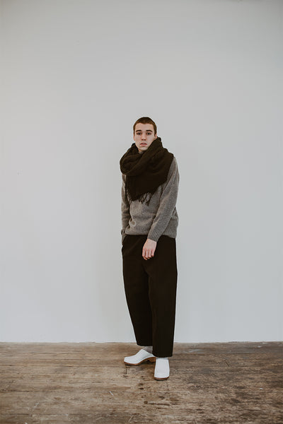 man wears a grey jumper with a black scarf, black trousers and white low heel men's classic style swedish clogs