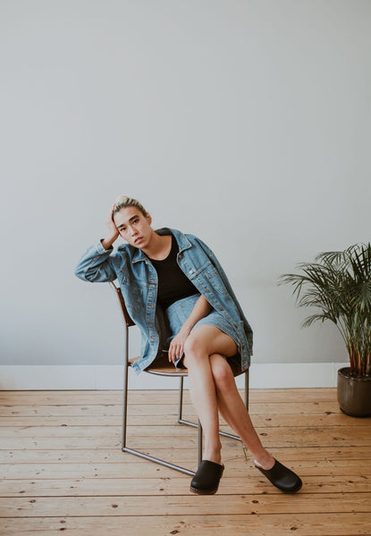 girl sits on a chair wearing a denim jacket and skirt with black low classic style swedish clog