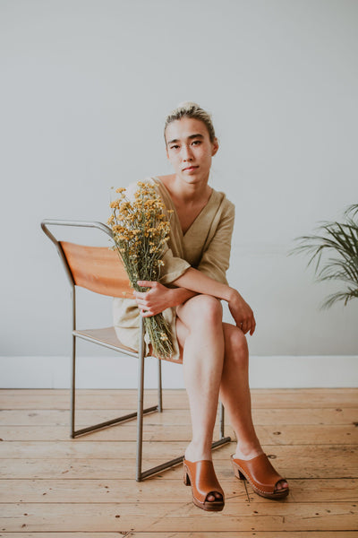 girl sits on a chair wearing a linen playsuit, holding a bunch of flowers wearing Tan brown cumin leather peep toe classic style mid heel Swedish women's clog