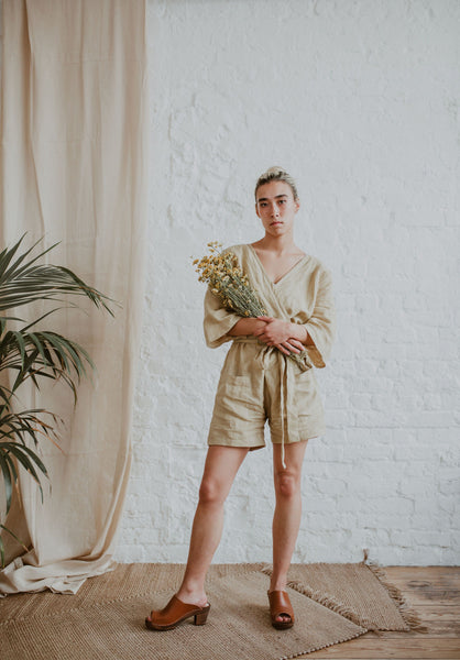 girl wearing a linen playsuit, holding a bunch of flowers wearing Tan brown cumin leather peep toe classic style mid heel Swedish women's clog
