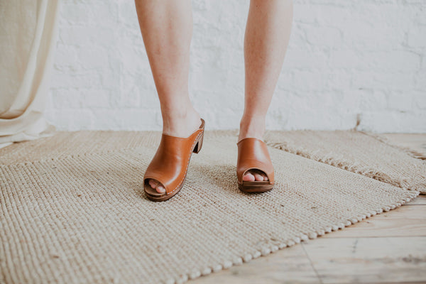Close up of woman's feet in Tan brown cumin leather peep toe classic style mid heel Swedish women's clog