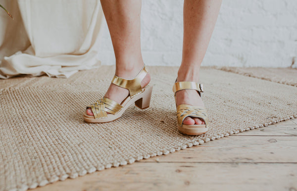close up of bride's feet wearing bridal wedding gold woven swedish clog sandals