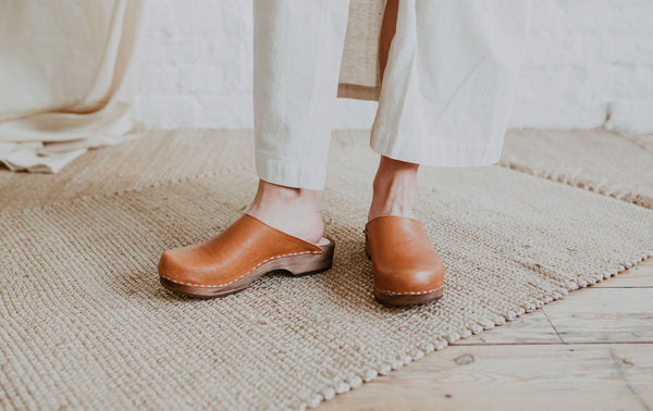 close up of woman's feet wearing a raw beige coloured linen skirt and cumin orangey tan brown low classic style swedish clogs