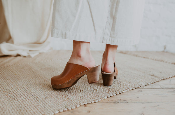 close up of woman's feet in cumin tan brown coloured classic style swedish clog with a mid heel