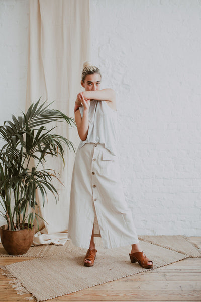 girl poses wearing a grey tank, raw cotton midi skirt and cumin tan brown woven leather mid heel clog sandals with an open back and toe